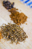 Cumin. Seed pile placed with other spices on a cutting board stock image