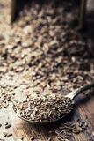Cumin.Caraway seeds on wooden table. Cumin in vintage bronze bowl and spoon Stock Photography