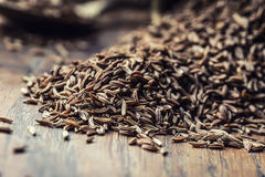 Cumin.Caraway seeds on wooden table. Cumin in vintage bronze bowl and spoon Royalty Free Stock Photography