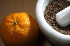 Cumin and orange. Cumin seeds in white marble shredder and orange royalty free stock images