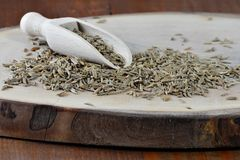 Cumin seed and wooden scoop on board Cuminum cyminum. Cumin seed and wooden scoop on wooden board Cuminum cyminum Royalty Free Stock Photography