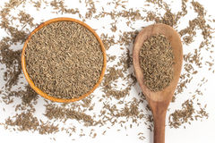 Cumin seeds into a bowl. Isolated in white background Royalty Free Stock Photo