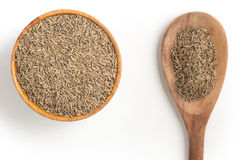 Cumin seeds into a bowl. Isolated in white background Royalty Free Stock Photography