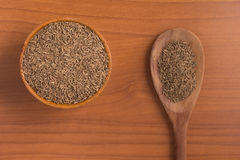 Cumin seeds into a bowl. Over a wooden table Royalty Free Stock Photo