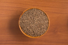 Cumin seeds into a bowl. Over a wooden table Royalty Free Stock Photography