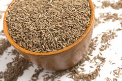 Cumin seeds into a bowl. In white background Stock Image
