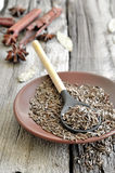 Cumin. Seeds in a brown plate on a rustic wooden background Stock Image