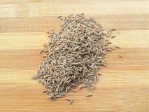 Cumin seeds heap on wooden background Stock Photos