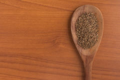 Cumin seeds into a spoon. Over a wooden table Stock Photography