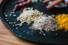 Cumin seeds surrounded by spices over black surface. Stock Photo