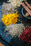 Cumin seeds surrounded by spices over black surface. Stock Photos