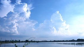 Cumlus och cirrusmolnmoln och blå himmel med flodrisfält royaltyfri bild
