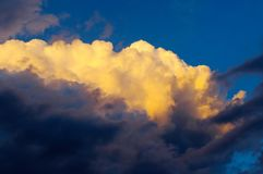 Cummullus clouds. Stormy cloud lit by last rays of sun Stock Image