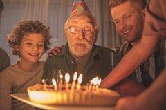 Cumpleaños de celebración de abuelo saliente con la familia Foto de archivo libre de regalías