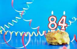 Cumpleaños de ochenta y cuatro años Magdalena con la vela ardiente blanca bajo la forma de número 84 imagenes de archivo