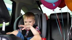 Cumpleaños del ` s del niño Montar a caballo feliz del niño en un coche Humor festivo, sonrisa, risa Globos en el coche almacen de metraje de vídeo