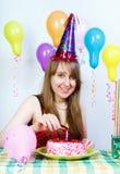 Cumpleaños. La muchacha atractiva feliz enciende una vela Foto de archivo