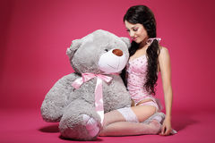 Cumpleaños. Muchacha sensual con Teddy Bear Sitting y la sonrisa. Precio Imagen de archivo libre de regalías
