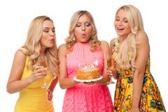 Cumpleaños rubio de la celebración de tres muchachas con la torta y el champán Foto de archivo