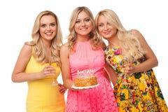 Cumpleaños rubio de la celebración de tres muchachas con la torta y el champán fotografía de archivo