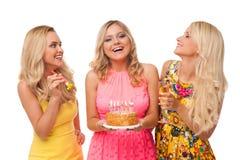 Cumpleaños rubio de la celebración de tres muchachas con la torta y el champán fotos de archivo libres de regalías
