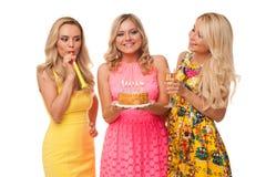 Cumpleaños rubio de la celebración de tres muchachas con la torta y el champán fotos de archivo