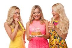 Cumpleaños rubio de la celebración de tres muchachas con la torta y el champán Imágenes de archivo libres de regalías