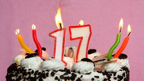Cumpleaños feliz 17 con la torta y velas en fondo rosado almacen de metraje de vídeo