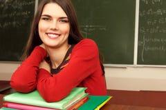 Cumplidor adolescente hermoso en sala de clase cerca de la sonrisa feliz del escritorio Fotos de archivo