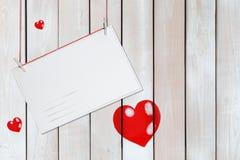 Cumprimentando o cartão de papel e três corações vermelhos no fundo branco de madeira com espaço da cópia imagens de stock royalty free