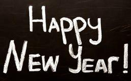 Cumprimento da mensagem do ano novo feliz escrito em um quadro-negro Fotos de Stock Royalty Free
