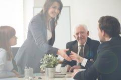 Cumprimento da mulher de negócios com colegas de trabalho Fotografia de Stock Royalty Free