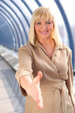 Cumprimento de meia idade de sorriso da mulher de negócios Foto de Stock