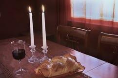 Cumprimento de Shabbat no por do sol: Chalá, vidro do vinho, duas velas do Lit Imagens de Stock Royalty Free
