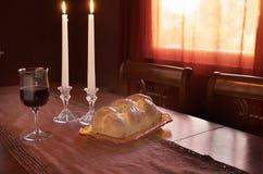Cumprimento de Shabbat no por do sol: Chalá, vidro do vinho, duas velas do Lit Fotografia de Stock Royalty Free
