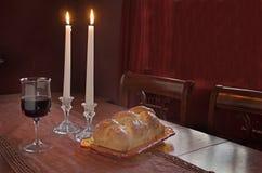 Cumprimento de Shabbat no por do sol: Chalá, vidro do vinho, duas velas do Lit Imagem de Stock Royalty Free
