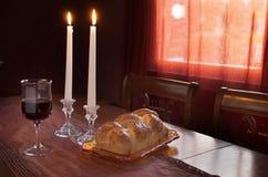 Cumprimento de Shabbat no por do sol: Chalá, vidro do vinho, duas velas do Lit Imagem de Stock