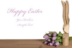 Cumprimento na Páscoa com um coelhinho da Páscoa de madeira e umas tulipas roxas Imagens de Stock