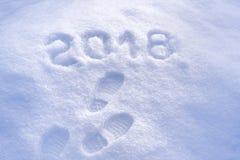 Cumprimento 2018, pegadas na neve, ano novo 2018, cartão do ano novo Imagens de Stock