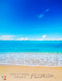 Cumprimentos de FLorida escrito em uma praia tropical Fotos de Stock Royalty Free