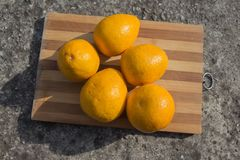 Cumquat或金桔与一半在一个木板 顶视图 平的位置样式 免版税库存图片