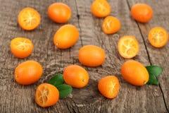 Cumquat或金桔与一半在老木背景 顶视图 平的位置样式 图库摄影