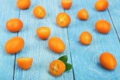 Cumquat或金桔与一半在蓝色木背景 库存图片
