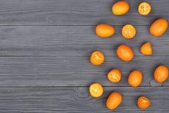 Cumquat或金桔与一半在黑木背景与拷贝空间您的文本的 顶视图 平的位置样式 免版税库存照片