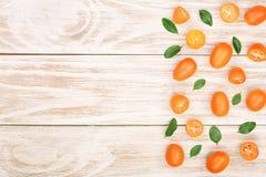 Cumquat或金桔与叶子在白色木背景与拷贝空间您的文本的 顶视图 平的位置样式 免版税库存图片