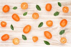 Cumquat或金桔与叶子在白色木背景 顶视图 平的位置样式 库存照片