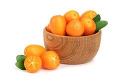 Cumquat或金桔与叶子在白色背景关闭隔绝的木碗  免版税库存照片