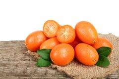 Cumquat或金桔与叶子在老木桌上有白色背景 图库摄影