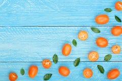 Cumquat或金桔与叶子在蓝色木背景与拷贝空间您的文本的 顶视图 平的位置样式 图库摄影
