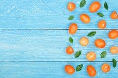 Cumquat或金桔与叶子在蓝色木背景与拷贝空间您的文本的 顶视图 平的位置样式 免版税库存图片